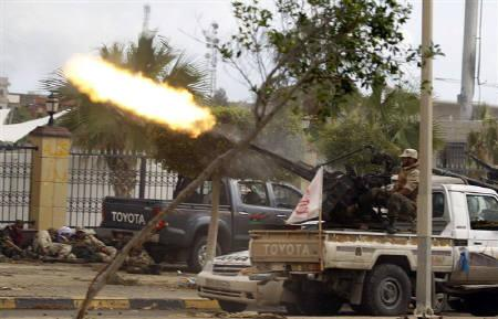 An anti-Gaddafi fighter fires a heavy machine gun during clashes with pro-Gaddafi forces at the front line in the center of Sirte October 13, 2011.  REUTERS/Thaier al-Sudani