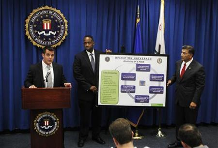 FBI Cyber Supervisor Agent Cameron Malin (L) speaks about the anatomy of a computer hack as U.S. Attorney Andre Birotte Jr.(C) and Assistant Director in Charge of FBI's Los Angeles Field Office Steven Martinez (R) hold a descriptive chart during an announcement of the arrest of Christopher Chaney, 35, of Jacksonville, Florida, in operation ''Hackerazzi'' for targeting celebrities with computer intrusion, wiretapping and identity theft, at the Federal Building in Los Angeles October 12, 2011.  REUTERS/Danny Moloshok