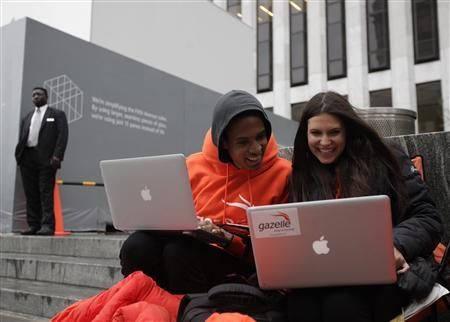 Keenen Thompson and Jessica Mellow (R) surf the web while waiting in line to buy an iPhone 4S at the Apple Store on 5th Avenue in New York, October 13, 2011.  iPhone 4S sales in stores begin October 14 in Japan, Australia, France, UK, Germany, Canada and the United States.  REUTERS/Brendan McDermid