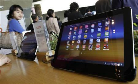 Visitors walk past Samsung Electronics' Galaxy Tab 10.1 tablets on display at a registration desk at the headquarters of South Korean mobile carrier KT in Seoul October 13, 2011. REUTERS/Jo Yong-Hak