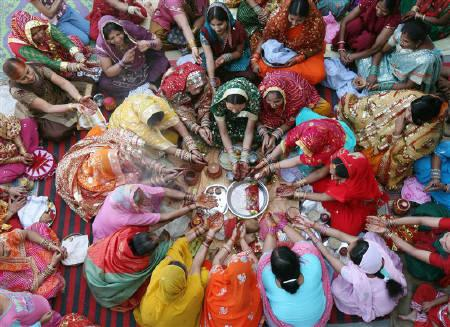 Women pray during the Hindu festival of Karva Chauth inside a temple in Chandigarh October 26, 2010.REUTERS/Ajay Verma/Files