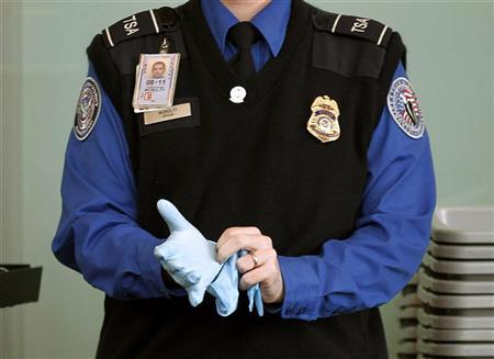 A TSA agent dons rubber gloves at a security checkpoint at Washington Reagan National Airport in Washington, November 22, 2010. REUTERS/Jason Reed