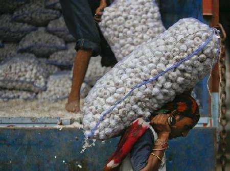 Labourers unload garlic from a supply truck at a wholesale vegetable market in Ahmedabad June 23, 2011. REUTERS/Amit Dave/Files
