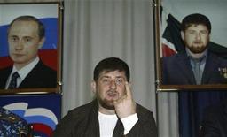 Президент Чечни Рамзан Кадыров сидит перед плакатами с изображением его самого и Владимира Путина на встрече с журналистами в Грозном 31 марта 2008. Путин собирается выделить госкредит размером до десятка миллиардов рублей на строительство в Чечне горнолыжного курорта. REUTERS/Said Tsarnayev