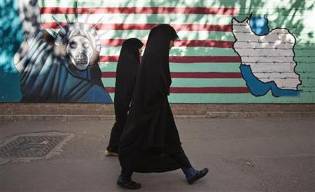 Iranian women walk past an anti-U.S. mural on the wall of the former U.S. embassy in Tehran October 12, 2011.  REUTERS/Morteza Nikoubazl
