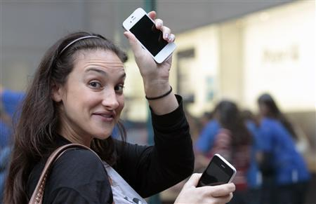 A customer shows off her new iPhone 4S as she leaves an Apple Store in New York, October 14, 2011. Apple Inc's new iPhone 4S went on sale in stores across the globe on Friday, prompting thousands to queue around city blocks to snap up the final gadget unveiled during Steve Jobs' life. REUTERS/Brendan McDermid