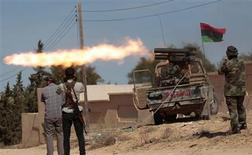 <p>Anti-Gaddafi fighters fire a rocket during clashes with pro-Gaddafi forces at the front line in Sirte October 15, 2011. REUTERS/Thaier al-Sudani</p>
