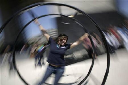 An ''Occupy Together'' activist spins in a (Rhoenrad), German Wheel during a gathering of demonstrators near the Monument of the Revolution in Mexico City October 15, 2011.  REUTERS/Bernardo Montoya