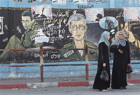 Palestinian women walk past a mural depicting captured Israeli soldier Gilad Shalit in Jabalya in the northern Gaza Strip October 15, 2011.   REUTERS/Mohammed Salem