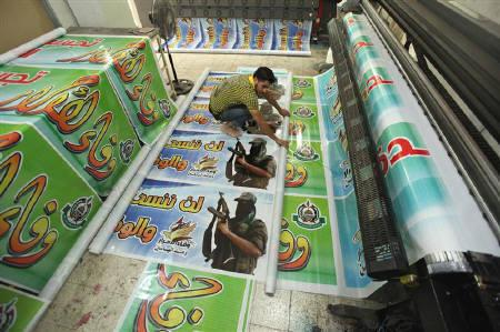 A Palestinian prints posters in preparation for a prisoner swap between Hamas and Israel, in Gaza City October 16, 2011. REUTERS/ Mohammed Salem