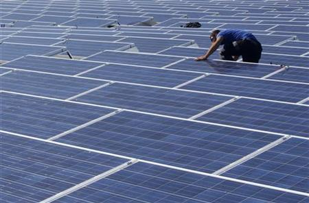 A worker installs solar panels on the roof of the Palexpo Exhibition Center in Geneva October 12, 2011. REUTERS/Denis Balibouse