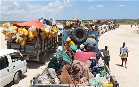 Internally displaced families board trucks as they travel back to their home regions from Ala-yasir camp closed by the al Shabaab militias, in Lower Shabelle, 50 km (31 miles) south of Somalia's capital Mogadishu, October 15, 2011. Kenyan troops have crossed into Somalia and have driven out al Shabaab militants from two bases near the Kenyan border in a joint operation with Somali soldiers, a Somali military commander said on Sunday. Picture taken October 15, 2011. REUTERS/Feisal Omar
