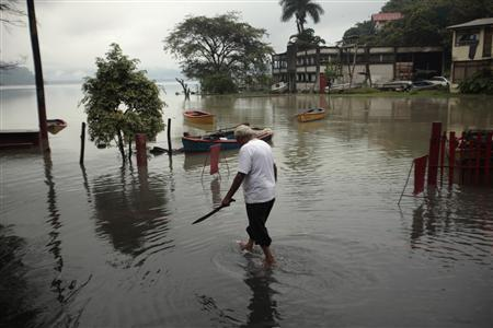 A man walks at the banks of the Amatitlan lake, 30 km (19 miles) of Guatemala City, October 16, 2011. Guatemalan authorities on Wednesday declared the country was in ''red alert'' after a tropical storm called 12E hit. Forty-four people have died and thousands are affected by the rains, according to the National Coordination of Disaster Reduction (CONRED). REUTERS/Jorge Dan Lopez