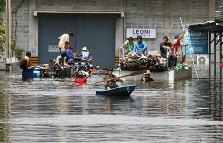Workers move goods from their warehouse at a flooded area in Nonthaburi province, on the outskirts of Bangkok October 16, 2011. REUTERS/Chaiwat Subprasom