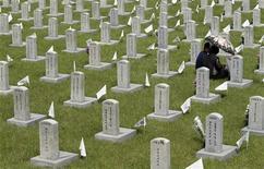Родственники солдата, погибшего во время Корейской войны 1950-53 годов, сидят около могилы в Сеуле, 6 июня 2011 года. Жительница Южной Кореи получила чуть более $4 в качестве компенсации от правительства за смерть ее брата во время Корейской войны 1950-53 годов.  REUTERS/Truth Leem
