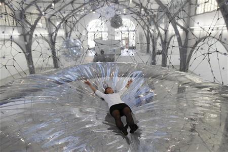 A museum staff member lies in an installation that is part of Tomas Saraceno's Cloud Cities exhibition at Hamburger Bahnhof in Berlin, September 14, 2011.  REUTERS/Thomas Peter