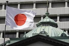 Японский флаг около Центробанка в Токио, 6 сентября 2010 года.  Правительство Японии в октябре понизило оценку экономики впервые за шесть месяцев, заявив, что замедление мирового роста отражается на темпах восстановления фабричного производства и экспорта страны. REUTERS/Toru Hanai