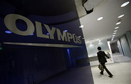 A man walks past a logo of Japanese camera and endoscope maker Olympus Corp at the company's headquarters in Tokyo in this May 17, 2011 file photo.    REUTERS/Yuriko Nakao/Files