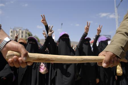 Anti-government protesters hold a baton as they surround women to protect them during a demonstration outside Yemen's foreign ministry to demand the ouster of President Ali Abdullah Saleh in Sanaa October 17, 2011. REUTERS/Mohamed al-Sayaghi