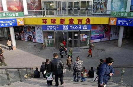 Customers walk out of a Wal-Mart store located in a shopping mall in Yanqing county of Beijing November 20, 2010. REUTERS/Alan Wheatley