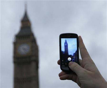A man holds up a mobile phone in central London December 7, 2009.  REUTERS/Andrew Winning