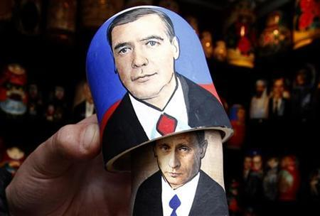A vendor demonstrates opening a traditional Matryoshka doll or Russian nesting doll, bearing the faces of Russian Prime Minister Vladimir Putin (underneath) and President Dmitry Medvedev at a souvenir market in St. Petersburg September 26, 2011. REUTERS/Alexander Demianchuk
