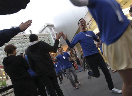 Apple employees greet customers waiting in line to purchase new iPhone 4S at Apple's flagship retail store in San Francisco, California October 14, 2011. REUTERS/Robert Galbraith