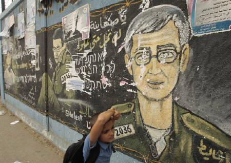 A Palestinian schoolboy walks past a mural depicting captured Israeli soldier Gilad Shalit in Jabalya in the northern Gaza Strip October 12, 2011. REUTERS/Ismail Zaydah