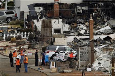 Investigators look over the remains of homes in a neighborhood that was destroyed when a natural gas pipeline ruptured and exploded, killing four people, and created a firestorm that destroyed 37 homes and injured more than 50 people last Thursday, in San Bruno, California September 13, 2010.  REUTERS/Robert Galbraith