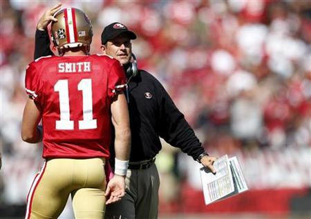 San Francisco 49ers head coach Jim Harbaugh (R) congratulates quarterback Alex Smith after a touchdown during the second quarter of their NFL football game against the Tampa Bay Buccaneers in San Francisco, California, October 9, 2011.   REUTERS/Beck Diefenbach