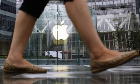 A woman passes in front of an Apple retail store at the financial district in Shanghai August 25, 2011. Apple Inc once more faces lofty expectations after smashing iPhone sales records, but Wall Street remains confident the world's largest technology company will deliver another bumper quarter. REUTERS/Carlos Barria/Files