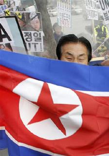 A protester holds a North Korean flag, which protesters were stopped from burning by the police, at a rally denouncing North Korea in Seoul November 24, 2010.  REUTERS/Kim Kyung-Hoon/Files
