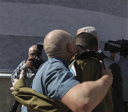 Gilad Shalit (R) is hugged by his father Noam at Tel Nof air base in central Israel in this handout released by the Israeli Government Press Office (GPO) October 18, 2011.  REUTERS/GPO/Handout