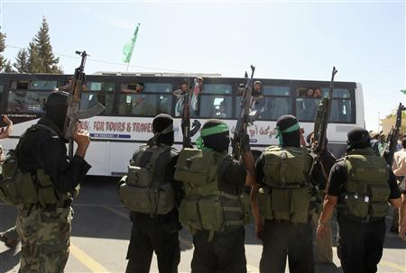 Hamas militants watch as a bus carrying Palestinian prisoners arrives in the Rafah crossing with Egypt in the southern Gaza Strip October 18, 2011.   REUTERS/Mohammed Salem
