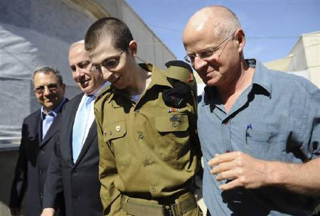 Gilad Shalit (2nd R) walks with his father Noam (R), Israel's Prime Minister Benjamin Netanyahu and Defence Minister Ehud Barak (L) at Tel Nof air base in central Israel in this handout released by the Prime Minister's Office (PMO) October 18, 2011. REUTERS/PMO/Handout