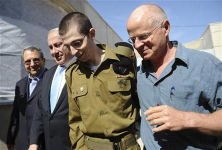 Gilad Shalit walks with his father Noam (R), Israel's Prime Minister Benjamin Netanyahu and Defence Minister Ehud Barak at Tel Nof air base in central Israel, in a photo released by the Prime Minister's Office, October 18, 2011. REUTERS/PMO/Handout