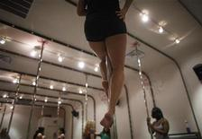 <p>Arlyne Chinn tries out a new move during an intermediate pole dancing class at Flirty Girl Fitness in Chicago February 17, 2009. REUTERS/John Gress</p>