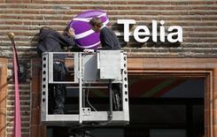 Рабочие устанавливают вывеску TeliaSonera на магазине в центре Стокгольма 12 мая 2011 года. Прибыль крупнейшего телекоммуникационного оператора Скандинавии TeliaSonera от основной деятельности в третьем квартале совпала с прогнозами, сообщила компания в среду, подтвердив также годовой прогноз. REUTERS/Bob Strong