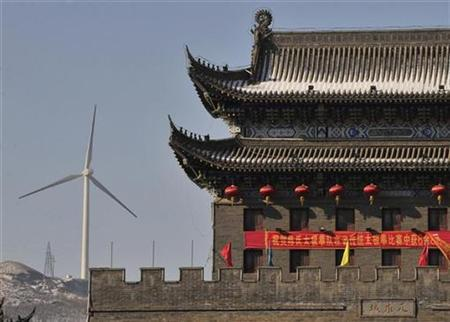 A wind turbine is seen near a gate of the ancient city of Wushu in Diaobingshan, Liaoning province January 18, 2011.  REUTERS/Sheng Li