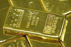 Килограмм золотых слитков на бирже золота в Сеуле, 9 авгутса 2011 г.Золото дешевеет в среду, так как инвесторы вновь обрели надежду на спасение еврозоны, проигнорировав снижение кредитного рейтинга Испании и отдав предпочтение акциям, однако слабый доллар оказал небольшую поддержку драгметаллу. REUTERS/Jo Yong hak