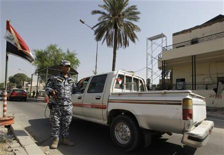 An Iraqi policeman uses a scanning device to inspect vehicles passing through a checkpoint in Baghdad September 6, 2011. REUTERS/Saad Shalash