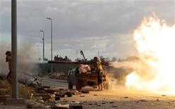 Anti-Gaddafi fighters fire a rocket during clashes with pro-Gaddafi forces at the frontline in Sirte October 19, 2011.   REUTERS/Thaier al-Sudani