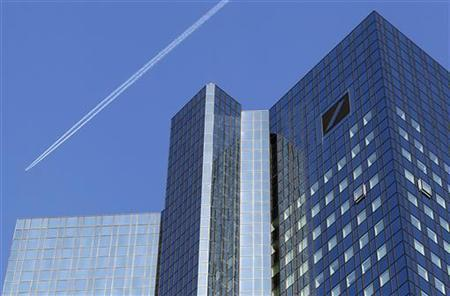 A jet leaves a vapour trail as it flies over the headquarters of Germany's largest business bank, Deutsche Bank in Frankfurt, October 14, 2011. REUTERS/Kai Pfaffenbach