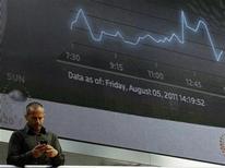 Мужчина стоит на фоне экрана с показателями индекса FTSE в деловом районе в Лондоне, 5 августа 2011 г. Европейские рынки акций закрылись в среду на положительной территории благодаря подъему котировок банков в надежде на то, что на воскресном саммите Евросоюза будет представлен обширный план выхода из кризиса долгов.REUTERS/Luke MacGregor