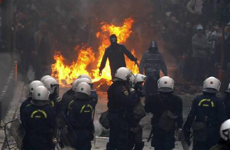 Youths stand in front of a burning barricade and taunt police during riots in Athens' Syntagma (Constitution) square October 19, 2011.  REUTERS/ Yannis Behrakis