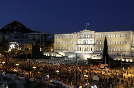 Protesters stand in front of the parliament during a rally against the austerity economic measures and corruption at Syntagma (Constitution) square in Athens June 26, 2011. REUTERS/John Kolesidis/Files