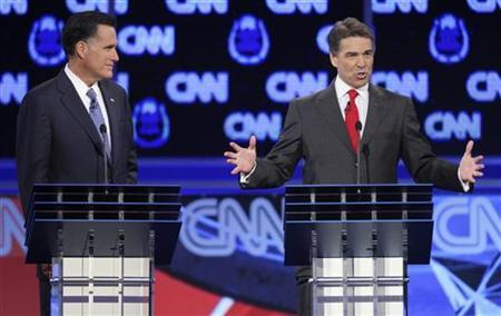 Texas Governor Rick Perry (R) speaks as former Massachusetts Governor Mitt Romney listens as they take part in the CNN Western Republican debate in Las Vegas, Nevada October 18, 2011. REUTERS/Steve Marcus