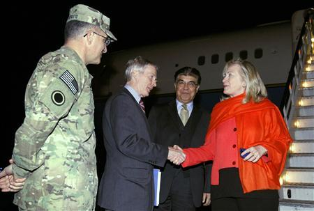 Secretary of State Hillary Clinton shakes hands with U.S. Ambassador to Afghanistan Ryan Crocker as Afghan chief of protocol Hamid Saddiq (2nd R) and Lt. General Curtis Scaparotti  (L) look on upon Clinton's arrival in Kabul October 19, 2011.  REUTERS/Kevin Lamarque