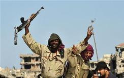 Солдаты, воюющие на стороне нового правительства Ливии, радуются падению Сирта, 20 октября 2011 года. Бывший ливийский лидер Муаммар Каддафи пойман, при этом он ранен в обе ноги, сообщил в четверг представитель Национального переходного совета Ливии Абдель Маджид. REUTERS/Esam Al-Fetori
