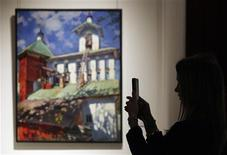 <p>A visitor takes a picture standing next to a painting by Russian artist Sergei Vinogradov at Sotheby's preview of upcoming major Russian art auctions in New York and London, at the Russian Academy of Arts in Moscow October 19, 2011. The auctions will be held in New York and London throughout November. REUTERS/Denis Sinyakov</p>